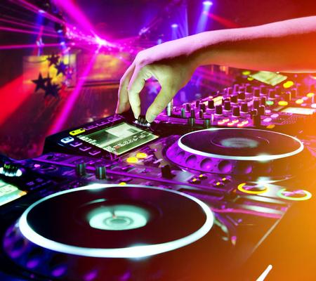 musica electronica: DJ mezcla la pista en el club nocturno en la fiesta. En el fondo espectáculo de luces láser