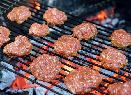 farci: Grilled burgers on a barbecue grill close-up