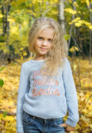 Retrato de la hermosa joven en el parque de otoño de los bosques