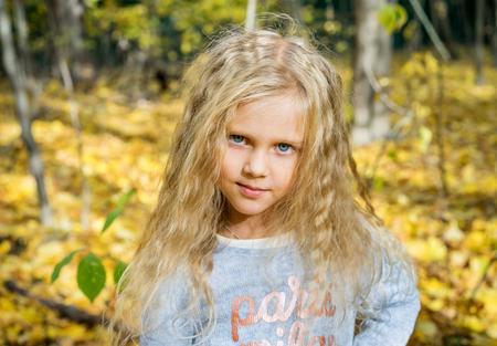 ojos azules: Retrato de la hermosa joven en el parque de otoño de los bosques