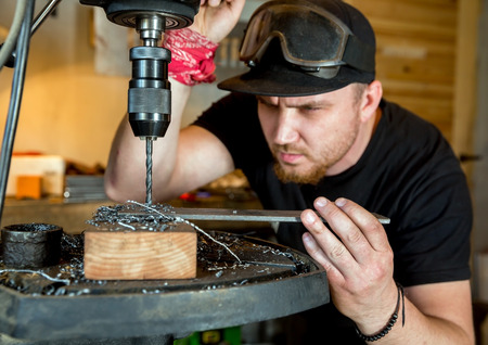 metall: Electric drilling machine with manual pressure, a man holding a metal part and the hole is drilled, strongly pressing drill to the workpiece surface