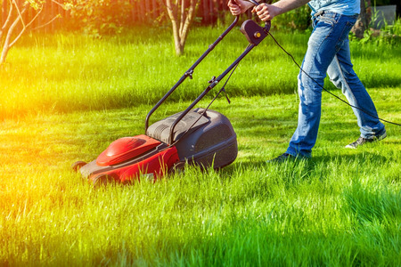 mows: Man in motion with lawnmower and mows green grass