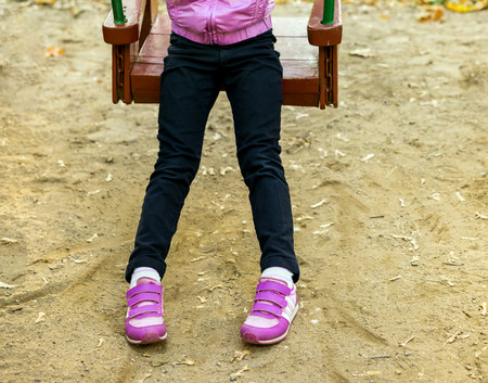 little  girls: Foot baby on swing in autumn park, swinging  at playground Stock Photo