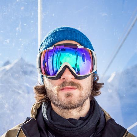anteojos de sol: Retrato de hombre joven con barba en la máscara de gafas de sol, se eleva a la cima en teleférico de cabina de pasajeros desde la estación de esquí en el fondo de las montañas y el cielo azul