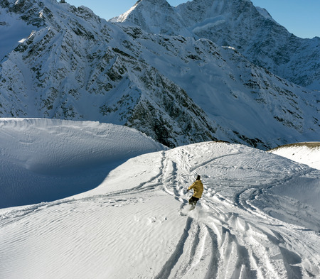 side effect: Freerider snowboarder moving down on the background of beautiful Caucasian mountains on Elbrus. Beautiful side effect sunbeam Stock Photo