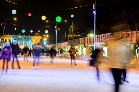People are skating in the park on winter skating rink