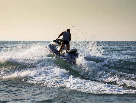 Silhouette of strong man jumps on the jetski above the water at sunset