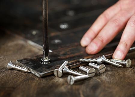 Worker spins screws in metal retro surface, using a manual flat screwdriver Foto de archivo