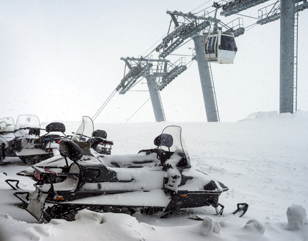 elbrus: Snowmobiles covered with snow on parking in the snowfall in the mountains Elbrus. Cableway  in motion on background