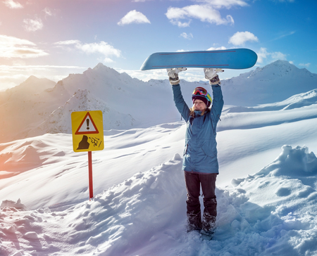 elbrus: Portrait of snowboarder woman on background beautiful landscape of snowy high mountains Elbrus standing with raised up snowboarding Stock Photo