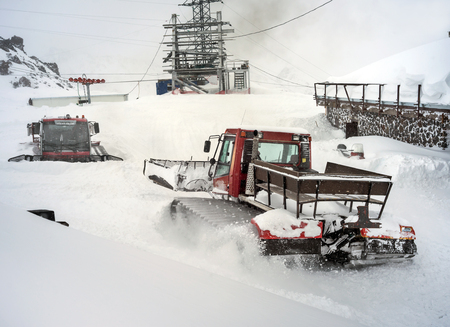snow grooming machine: Snowcat in motion in snowfall on slope in the mountains at skiing resort Elbrus, preparing and clearing the track Stock Photo