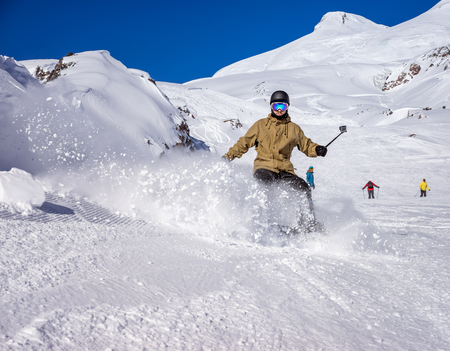 freerider: Freerider snowboarder moving down in snow powder and relieves himself on the video with the help of a stick self on the winter resort Stock Photo