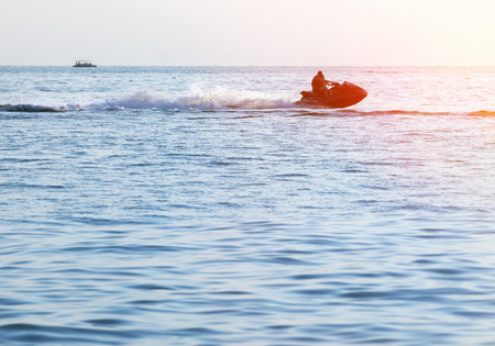 jetski: Silhouette of a man and young girl in motion on jetski on the sea