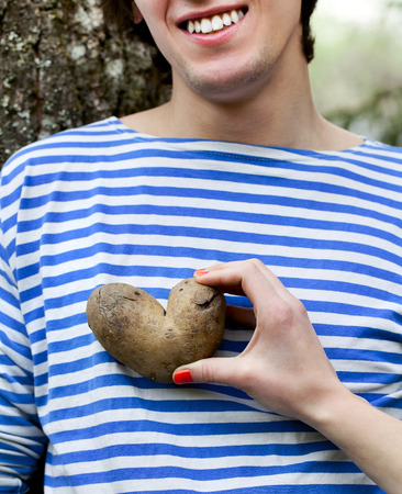 woman's hand: Smiling young man and womans hand holding a potatoes in the form of heart in garden Stock Photo