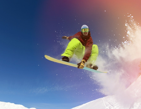 snowboard: Jumping snowboarder keeps one hand on snowboard in mountains in ski resort on blue sky background Stock Photo