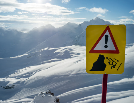 ski traces: Warning sign of danger for skiers of standing on precipice on background of beautiful Caucasian mountains on Elbrus Stock Photo