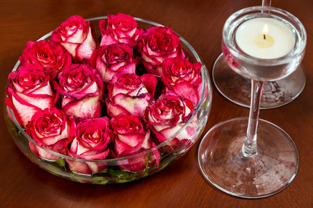 lot of: Red rosebuds in glass vase with water on wooden table with lit candle. Valentines day romantic background, top view Stock Photo