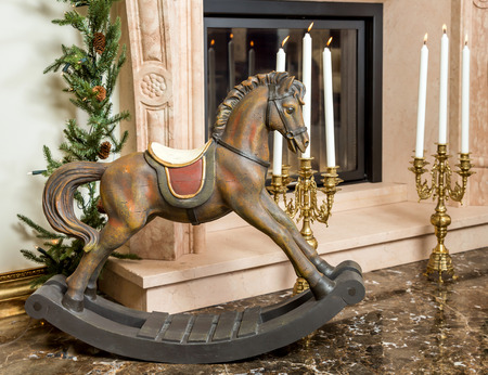sconces: Old wooden rocking horse for children on the background of burning candlesticks in sconces near the fireplace