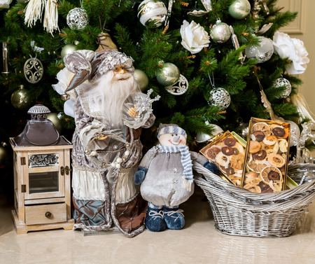 decorate: Santa Claus, basket with mandarins and lantern-candlestick with gifts in New Years holiday under Christmas tree