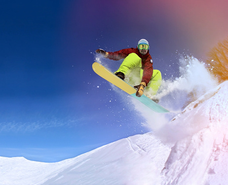 Jumping snowboarder keeps one hand on snowboard in mountains in ski resort on blue sky background Archivio Fotografico