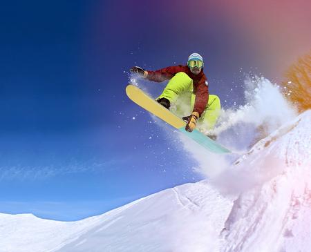 Springen snowboarder houdt een hand op een snowboard in de bergen in het skigebied op de blauwe hemel achtergrond