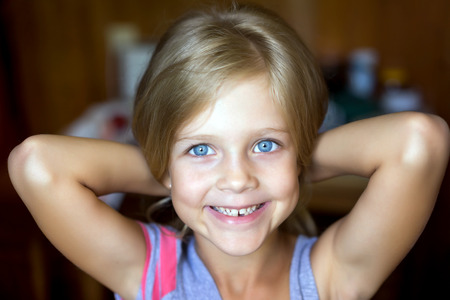 keep an eye on: Portrait of young attractive beautiful blonde girl with blue eyes with a smiling and positive expression of the face