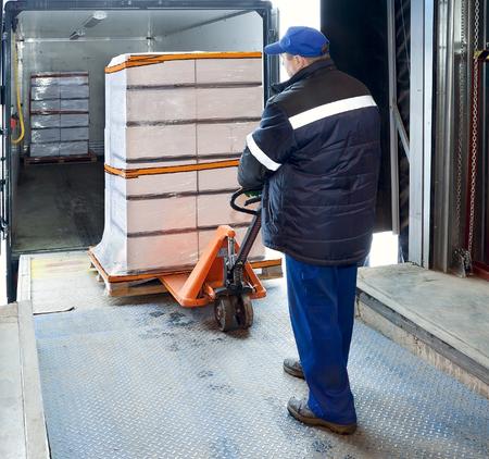 Worker loading truck on forklift 스톡 콘텐츠