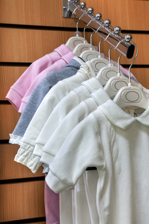romper: Collection of jumpsuits baby clothes on hangers in store closeup Stock Photo