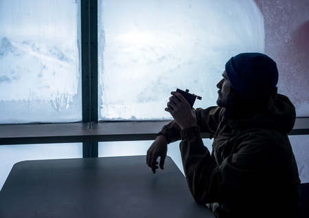 man looking out: Bearded man traveler inside the hotel with flask in his hand looking out the window at the beautiful snow-covered mountain landscape Stock Photo