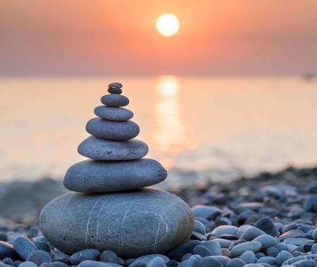 Piramida z kamieni do medytacji leżącej na brzegu morza o zachodzie słońca