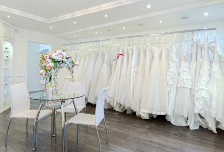 wedding table decor: Collection of wedding dresses in the shop