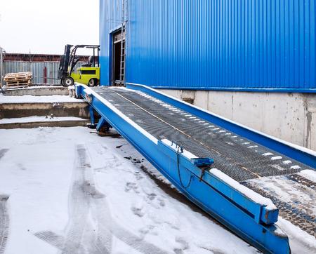 montacargas: Carretilla elevadora de pie en la entrada de un gran almac�n moderno