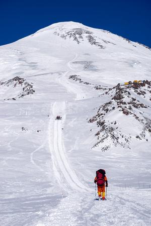 snowcat: Climbing lone alpinist in the Caucasus mountains Elbrus, climb up the trail snowcat