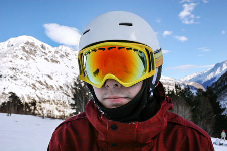 ski mask: Portrait of young snowboarder in sunglass mask at the ski resort of Elbrus on the background of mountains and blue sky