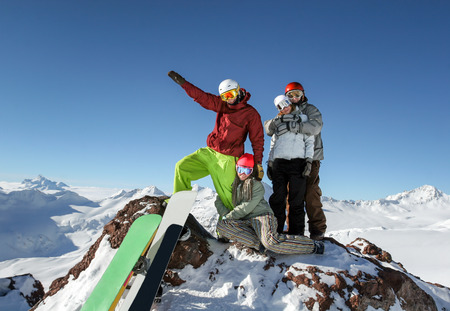 top mountain: Young friends snowboarders standing together on the top of the slope on a background of mountains and blue sky