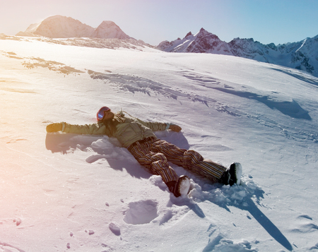 woman laying: Silhouette of young woman snowboarder, lying down on snow, moving her arms and legs up and down creating a snowy angel figure at the ski resort of Elbrus