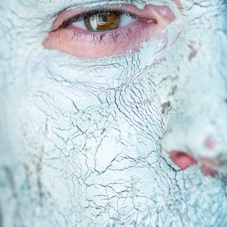face mask: Men face closeup on facial blue clay mask. Treatment and care for the face skin