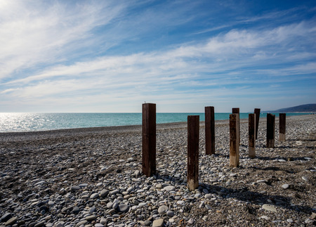wood pillars: Wooden poles stand on marine pebbles on background beautiful seascape at sunset day in summer season Stock Photo