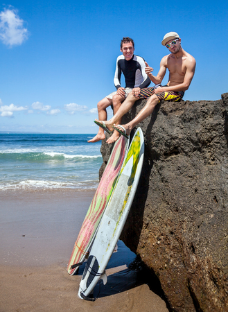 two person: Two friend surfer sitting on rock showing sign OK. Two surfboards standing on the sand, leaning on a rocky big stone Stock Photo
