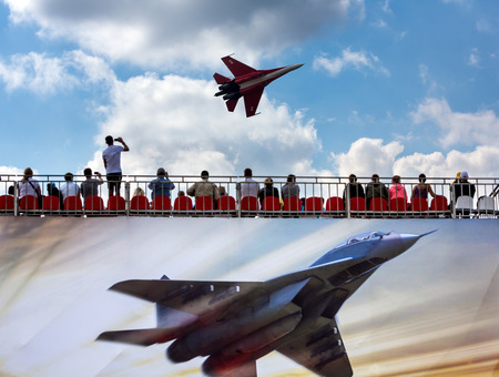 airshow: ZHUKOVSKY, MOSCOW - AUG 16: Spectators in the stands and Russian fighter aircraft MIG-29 at AirShow Furious 2014 on August 16, 2014 in Zhukovsky, Moscow region, Russia
