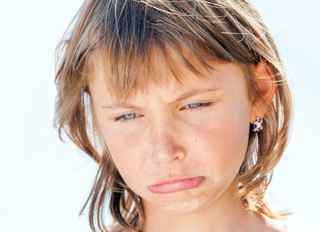 disadvantaged: Offended face of young beautiful girl close-up on the background Stock Photo