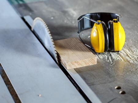 ruido: madera de sierra circular en el taller de carpintería y protección para los oídos contra el ruido en el trabajo Foto de archivo