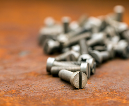 sheet metal: Pile of bolts with thread on rusty metal table Stock Photo
