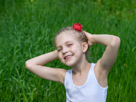 hands on head: Portrait of beautiful young girl in park with braids and red flower in summer time on a background of green grass