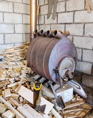 flue season: Modern wood burning cast iron oven in the boiler room for heating of rooms Stock Photo