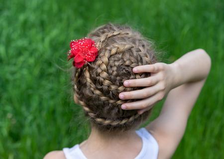 Modische Frisur Nahaufnahme mit Zöpfen und roten Blume auf einem jungen Mädchen auf einem Hintergrund von grünem Gras. Rückansicht