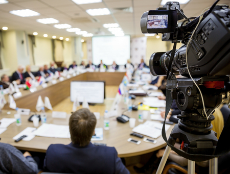 broadcasting: People sitting at a round table in the negotiations in the conference room. In the foreground TV video equipment for shooting Stock Photo