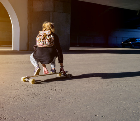 Young girl riding on a longboard on a paved road in summer time in city