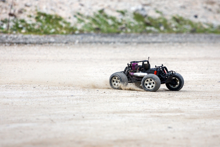 controlled: Radio controlled car model in race quickly moving on the sandy road Stock Photo