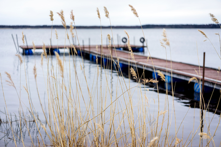 foreground focus: Pier for pleasure and fishing boats on shore of Lake Ladoga in Karelia. Soft focus. In the foreground the tall grass